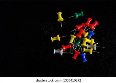 Top view of colorful thumbtacks on a black background