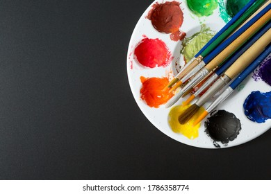 Top view of Colorful Watercolor palette and paintbrush on a black background and copy space