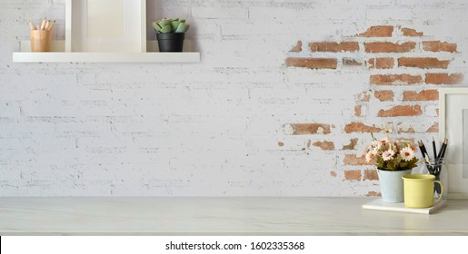 Top view of comfortable vintage workplace with office supplies and copy space on white table and brick wall background