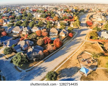 Top view community playground near residential area with row of single-family detached house and colorful autumn leaves. Urban sprawl subdivision in background