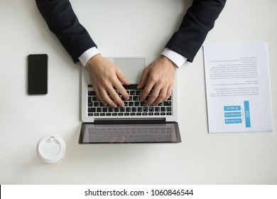 Top view of company CEO typing at laptop, handouts papers, coffee and smartphone around. Businessman working at office desk. Concept of hard work, flat lay, close up view