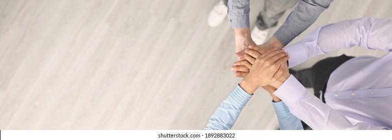 Top-Ansicht von Firmenangestellten, die vor allem Hände zusammenlegen. Support und Teamarbeit. Arbeiter in Anzügen. Kopiert Platz auf der linken Seite. Entwicklung und Erfolg. Konzept für Wachstum in Unternehmen und Karriere