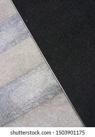 Top view comparative texture of black rubber flooring ethylene-propylene diene (EPDM) and granite tile flooring. Exterior design concept.