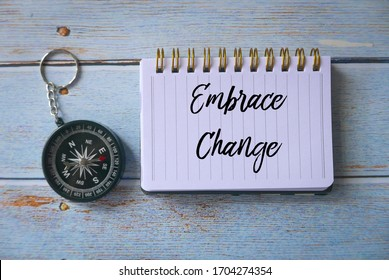 Top view of compass and notebook written with Embrace Change on wooden background.