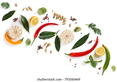 Top view of composition of herbs and spices ( pepper, basil, cardamom, bay leaf, garlic, lemon, dill and chilli ) isolated on white background.