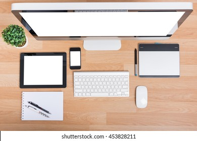 Top view computer PC monitor and keyboard with Phone, magic mouse and tablet on wooden desk