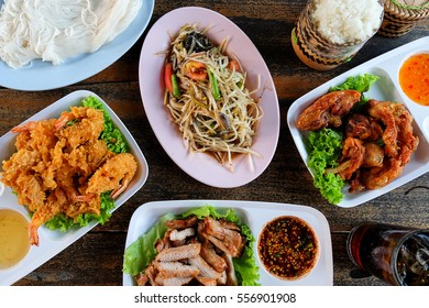 top view concept of hipster special thai food (batter-fried prawns,spring rolls,fried chicken,spicy green papaya salad,sticky rice) on wooden table.