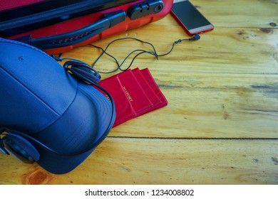 Top view conceptual of preparation for oversea holidays trip at year end. Red luggage besides grey cap earphones smartphone and passport on wooden table. Selective focus.