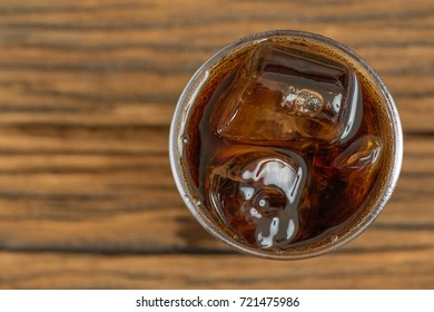 Top view of condense glass with cola soda drink with ice cube on rustic wooden table with empty space