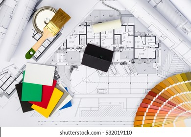 Top View of Construction plans with whitewashing Tools,Colors Palette and Miniature House on blueprints; Architectural and Engineering Housing Concept.