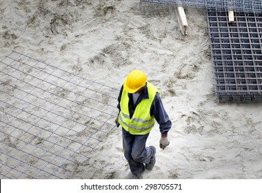 Top view of construction worker carrying reinforcement mesh at building site
