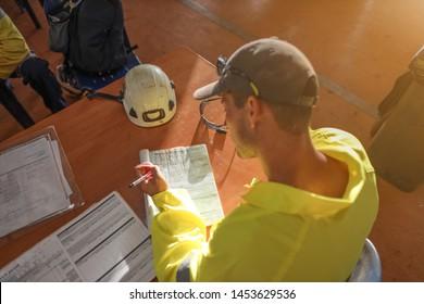 Top view of construction worker setting on the chair writing Job Hazard risk Assessment (JHA) working at height permit prior commence work of each task construction site