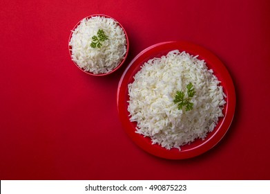 Top view of Cooked plain white basmati rice in red bowl and plate on red background