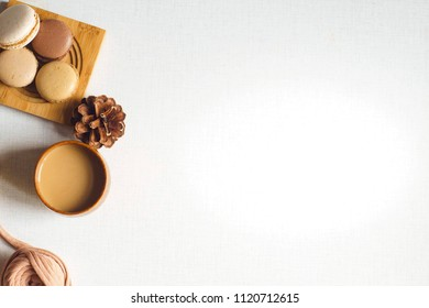 Top view of a cookie with latte and spruce cone and a yarn. Espresso, four cookies and spruce cone and a tangle on the white desk. Sunny morning. Flat lay with copy space for text.