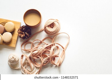 Top view of a cookie with latte and spruce cone and a yarn. Coffee, four macarons and spruce cone and a tangle on the white table. Sunny day. Flat lay with copy space for text.
