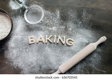 top view of cookies in forms of letters with powdered sugar and rolling pin, cookie dough