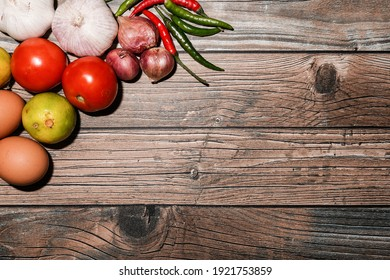 Top view of Cooking background , home cooking concept . Ripe tomato, onion, garlic, chilli, eggs and lime on the wooden background with copy space.