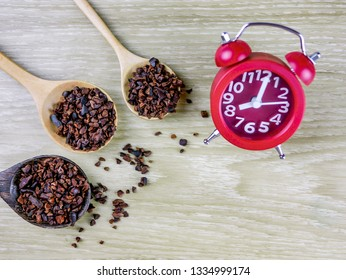 Top view copy space on Benefits of healthwork Organic Cacao nips concept : rough grinding superfood Cacao nips in wooden spoon with red alarm clock