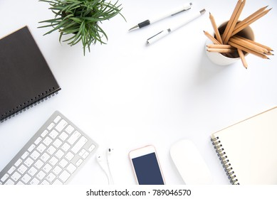 Top view with copy space, working desk with laptop,cell phone,notebook pencil and coffee on white background