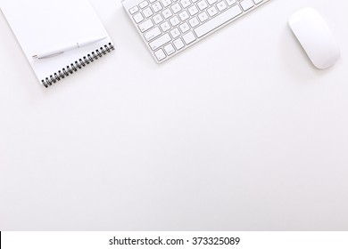 Top View of Corporate Executive Working Place with Keyboard Notepad Pen and Mouse on White Desk