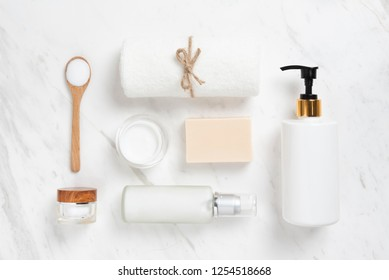 Top view of Cosmetic bottles, soap, wooden spoon and towel on white marble background. Spa products.