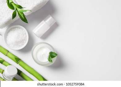 Top view of cosmetic products with natural ingredients on white background for natural beauty. High angle view of spa setting with moisturizer and bamboo sticks. Beauty spa background with copy space.