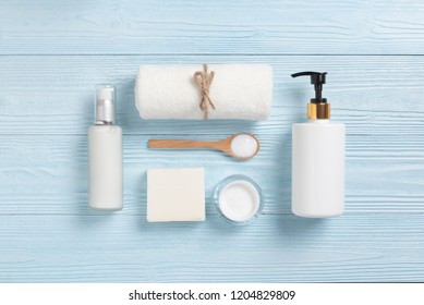 Top view of Cosmetic Spa products on blue wood background. Towel, cream bottles, wooden spoon, soap with Copy space.