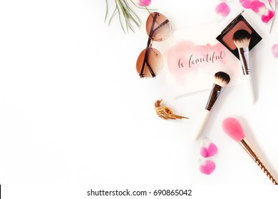 Top view of cosmetics and female accessories on white with pink petals and inspirational words written in calligraphy style `Be beautiful`. Beauty blog flat lay concept.