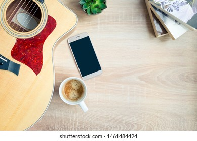 Top view of cosy home scene. Guitar, books, cup of coffee, phone and succulent plants over wooden background. Copy space, mock-up.