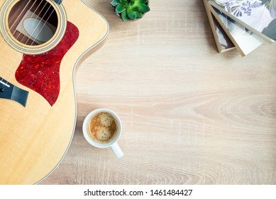 Top view of cosy home scene. Guitar, books, cup of coffee and succulent plants over wooden background. Copy space.