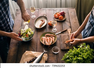 Top view couple cooking together delicious and healthy dinner shrimp and salad of vegetables on a wooden table in home kitchen