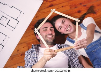 Top view of a couple in love, lying on the floor, who have just bought a house and is moving. The bride and groom smile and hold the house-shaped meter in their hands.