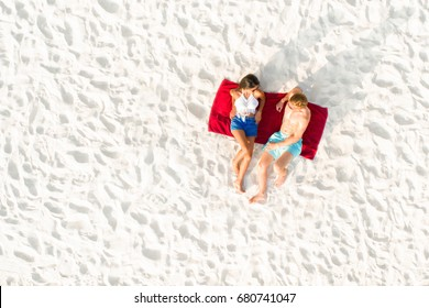 Top view of couple lying on white sand beach taking a sunbath in summer