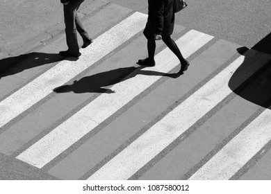 Top view of couple man and women people walk across crosswalk in the city street. Sunday.