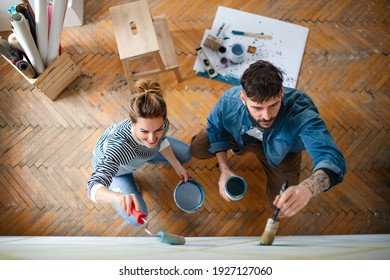 Top view of couple painting wall indoors at home, relocation and diy concept.