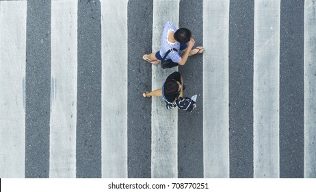 the top view of couple people walk across the pedestrian crosswalk in white and grey pattern