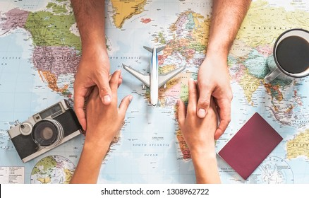 Top view of couple planning their vacation with world map - Lovers getting ready for the next world tour - Concept of adventure, tourism, and traveling people lifestyle