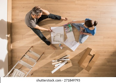 top view, couple sitting on the floor of their new home on a sunny morning and reviewing blueprint to choose the decoration of their new interior.
