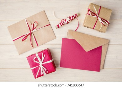 Top view of craft envelopes and gift boxes on wooden background