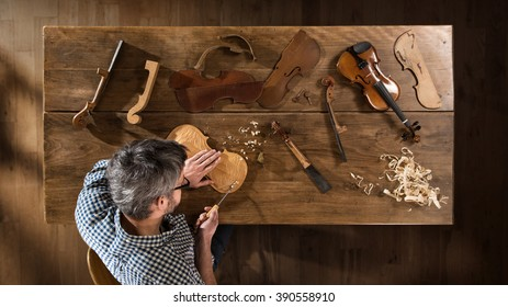 Top view. Craftsman luthier working on the creation of a violin. He sits at a wooden table in his workshop, various tools and instrument are placed on the workbench
