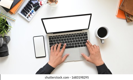 Top view Creative man's hands typing on computer laptop with white blank screen that putting on white working table surrounded with coffee cup, empty screen smartphone and accessories.