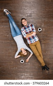 Top view creative photo of beautiful young couple on vintage brown wooden floor. Couple lying with cup of coffee