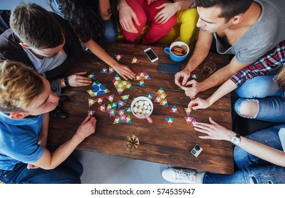 Top view creative photo of friends sitting at wooden table. Friends having fun while playing board game.