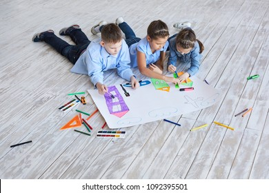 Top view creative photo of little boy and girl on brown wooden floor. children draw together on a large sheet of paper