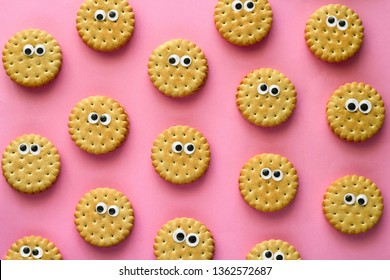 top view creative still life flat lay cookies    with googly eyes rows  pattern on vibrant pink background