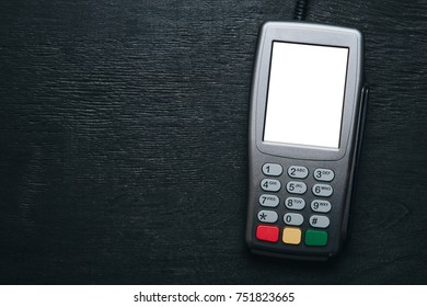 Top view to credit card terminal on dark wooden desk. Mockup witn clear white mockup screen template