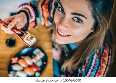 Top view Crop woman eating sushi