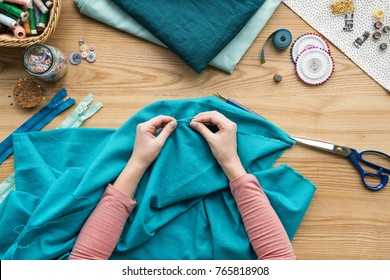 top view of cropped female hands sewing fabric with needle at seamstress workplace