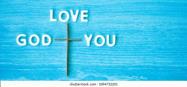 Top view of Cross and GOD LOVE YOU words on blue wooden background.Jesus Christ cross. Easter, resurrection concept.