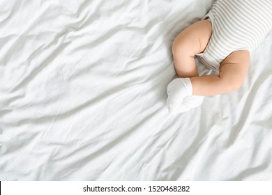 Top view of crossed legs of newborn baby lying on bed in bodysuit and socks, panorama with free space